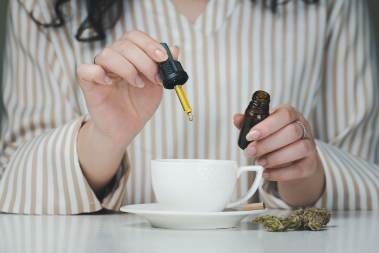 A woman wearing pajamas adds hemp oil to her drink
