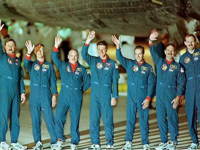 Seven astronauts standing next to each other and waving the camera.