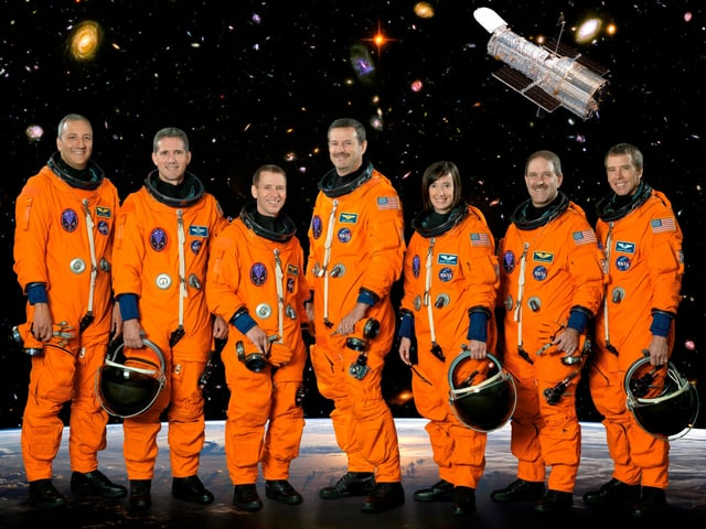 Seven astronauts standing next to each other in protective clothing.