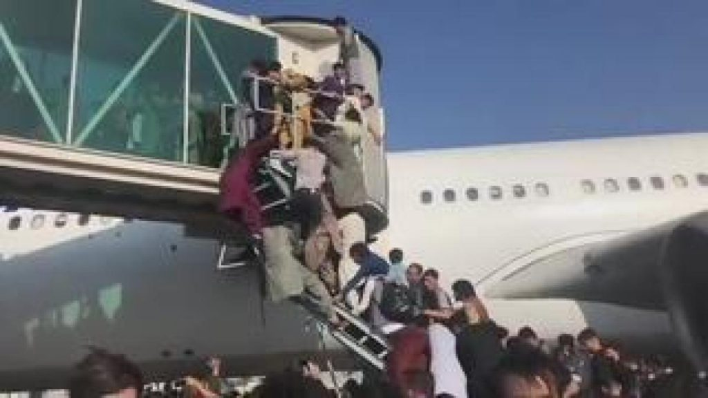 Afghanistan: Chaos at Kabul Airport - People Climbing Wings