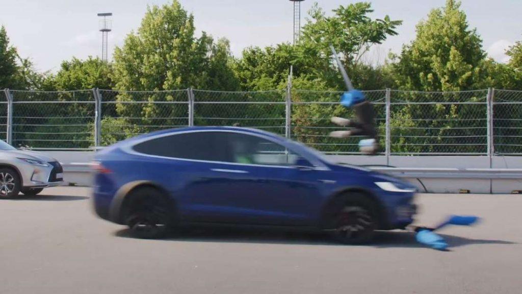 A Tesla Model X knocks on a pedestrian toy.