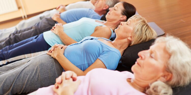 Many women and men lie on yoga mats with their hands folded on their stomachs